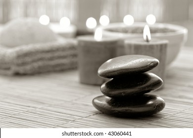 Black polished hot massage stone cairn with burning candles for a soothing spiritual Zen relaxation and meditation session in a spa