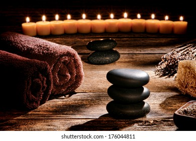 Black polished smooth hot massage stones in a Zen inspired cairn on a vintage wood boards table in a rustic natural and holistic spa for a traditional relaxation and health rejuvenation treatment