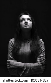 Black and whit? portrait of a young girl, woman. Full face, girl looking up