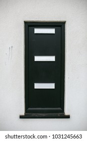 Black postbox in a white wall