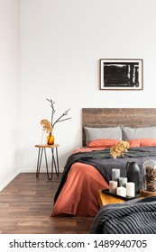 Black poster on the white wall of elegant bedroom interior with king size bed with wooden headboard and nightstand with flowers in vases