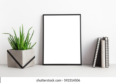Black poster or photo frame, books and a plant in concrete flowerpot. Mock up.