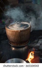 black pot boiling water for cooking rice on the fired stove next to firewood pile, Thailand north east local method