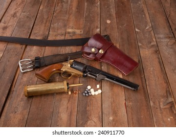 A black powder gun with holster on wood.