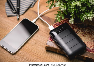 Black power bank connected with USB cable. Charging smartphone with power bank. Shallow depth of field focused on power bank display.
