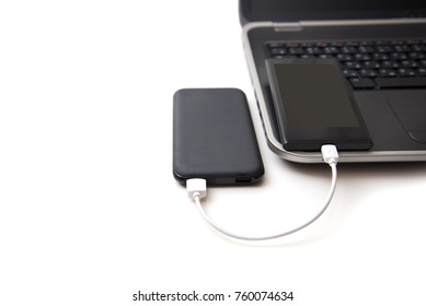 Black power bank and smartphone on computer