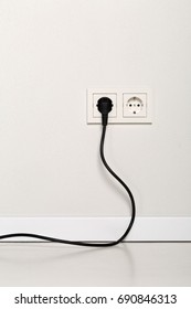 Black power cord cable plugged into european wall outlet on white plaster wall with copy space