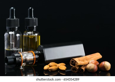 Black powerful electronic cigarette next to liquids, with the taste of nuts and carica