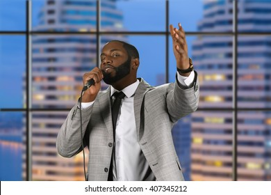 Black preacher speaking into microphone. Bearded preacher on evening background. Evening prayer in city church. Strengthen your faith.