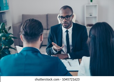 Black, professional, afroamerican, serious lawyer in classic suit making consultation to bisnesspeople who want to make a deal about their business, together sitting in work place, station