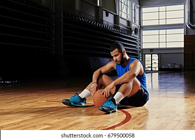 Black professional basketball player sits on a floor in a game hall.