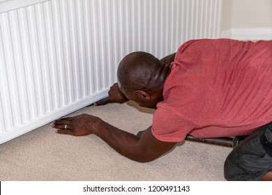A black professional carpet fitter, wearing a short-sleeved red shirt, kneels on the floor while working to fit a beige carpet under a tightly fitted white radiator.