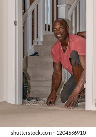 A black professional carpet fitter, wearing a short-sleeved red shirt, kneels on the floor while working to fit a beige carpet.