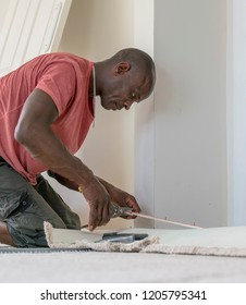 A black professional carpet fitter, wearing a short-sleeved red shirt, kneels on the floor while measuring to fit a beige carpet. The door, taken off its hinges, is leaning against the wall.