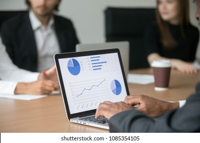 Black project manager working on computer analyzing statistics on screen at multiracial meeting, african employee using laptop preparing financial marketing report, software for data analysis concept