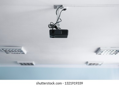 Black projector on a ceiling in a classroom.