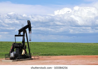 Black pump jack on a green prairie with a large copy space