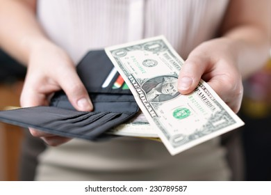 Black purse with money in woman`s hand