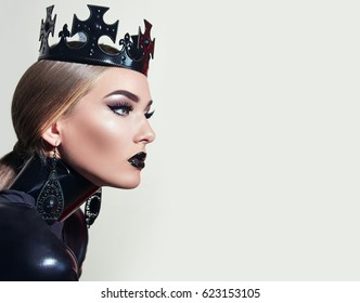 Black queen. A stern look. Black crown. A princess. Maleficent. Girl with a black crown decorated with precious stones sitting in studio on light background. Dark lipstick.