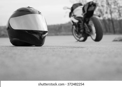 Black race helmet and motorcycle on road. Black and white.