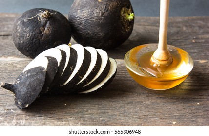 black radish with honey wooden background