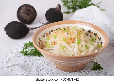 Black radish salad with fried onions in a ceramic bowl