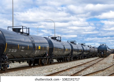 Black railway tank cars used to transport petroleum products. Several cars visible on two separate sets of tracks. Identification markings have been removed, only technical information remains.