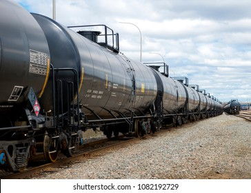 Black railway tanker cars to transport petroleum products. Several cars visible on two separate sets of tracks. Identification markings have been removed, only technical information remains.