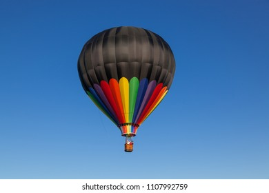 A black and rainbow hot air baloon floating on a calm clear blue sky day.