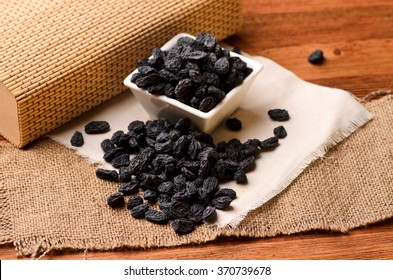 black raisins on a brown wooden table and a white canvas, close-up