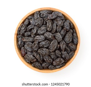 black raisins in the wooden bowl, isolated on white background, top view