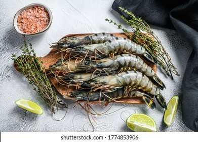 Black raw tiger prawns, shrimps on a cutting board. Gray background. Top view