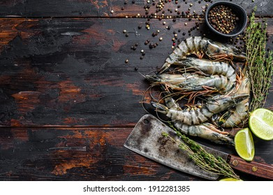 Black raw tiger prawns, shrimps with thyme and pepper. Black wooden background. Top view. Copy space