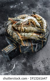Black raw tiger shrimps. Black background. Top view