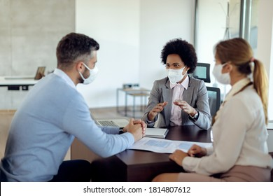 Black real estate agent and a couple wearing protective face masks while communicating during the meeting in the office.  - Shutterstock ID 1814807612