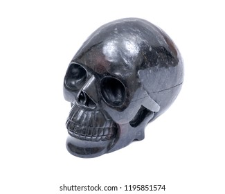 Black realistic carved stone skull with Astrophyllite blades from Russia, isolated on white background.