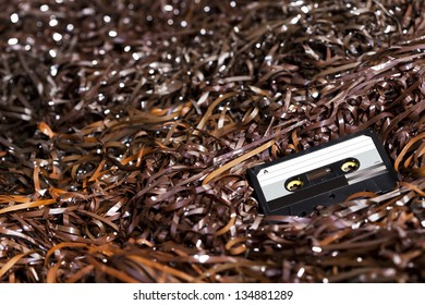 Black recordable plastic audio cassette resting on a large amount of magnetic audio tape. Selective focus on foreground.