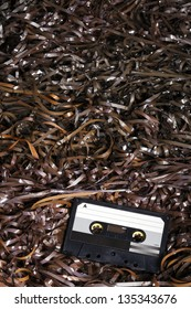 Black recordable plastic audio cassette resting on a large amount of magnetic audio tape.