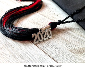 Black and red 2020 graduation cap with tassel on a wooden background