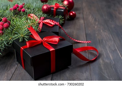 Black and red Christmas background. black gift box,  balls, fir branches,red Christmas decorations on the dark wooden background  copy space