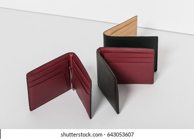 black and red colored leather wallet on the grey background.