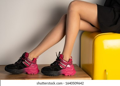black and red sneakers on the legs of a girl, side view, light background