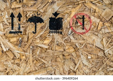 Black and red spray painted symbols showing keep upright, keep away from water, do not overload and do not lift on the side of a wooden box made from wood shavings.