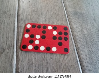 black, red, and white game pieces on brown wood floor