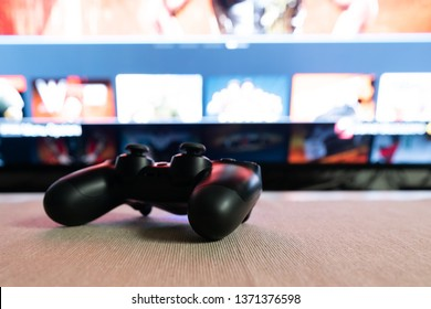 Black remote video game controller resting on the table, television in the background