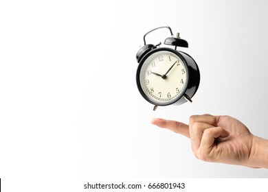 Black retro alarm clock floating on man's finger with white background
