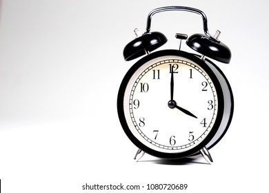 Black retro alarm clock on combination of gray and white background with copy space for text