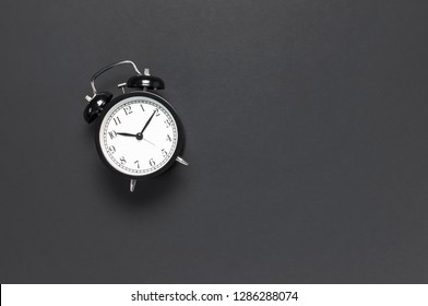 Black retro alarm clock on gray dark background top view Flat lay copy space. Minimalistic background, concept of time, deadline, time to work, morning