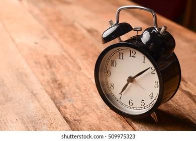 Black retro alarm clock on wooden table