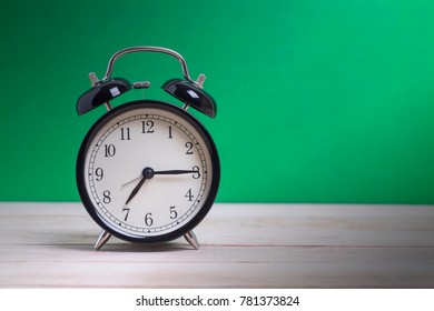 A Black Retro alarm clock on wooden board with green background